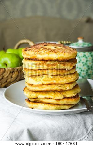 Stack of golden delicious homemade cottage cheese fritters or pancakes on white plate rural kitchen interior cozy atmosphere kinfolk