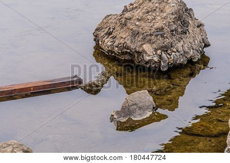Scrap of wood floating in river next to large stone