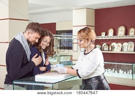 Expert help. Female jeweler showing engagement rings to a young loving couple at the store