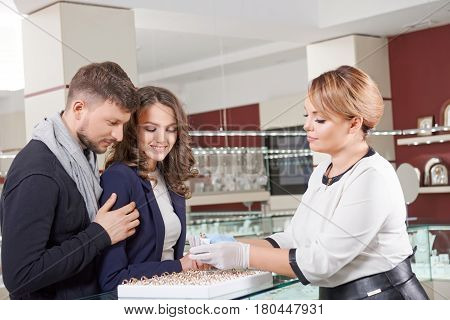 Special choice. Professional female jeweler assisting young couple in choosing engagement rings