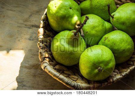 Ripe green organic pears in vintage wicker basket on aged wood kitchen table sunlight flecks rustic style closeup copyspace