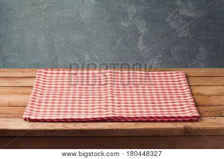 Empty wooden deck table with checked tablecloth over blackboard background for product montage display
