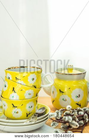 Pretty yellow tea set with stacked cups saucers and pot floral ornament rustic kitchen interior soft sunlight spots spring Easter brunch teaparty
