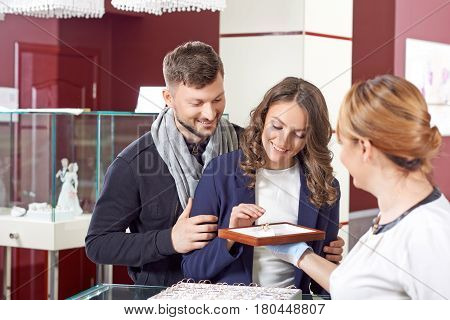 Beauty comes at a price. Horizontal portrait of a beautiful couple going to try engagement rings before buying