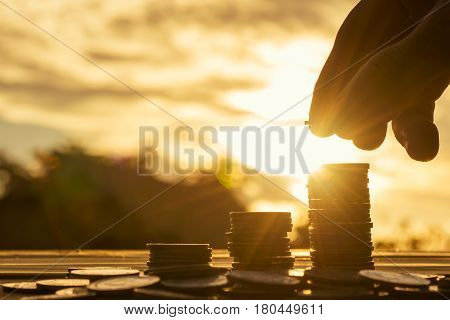 Saving money concept preset by Male hand putting money coin stack growing business. Close up of hand on sunset background, money concept, Business Finance and Money concept, Save money for prepare in the future. money silhouette.