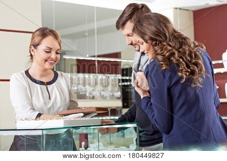 Momentous choices. Female clerk helping young couple in choosing engagement rings at the store