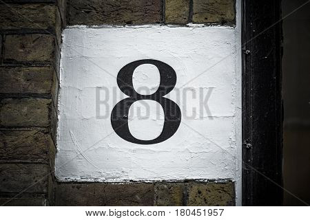 Number eight hand painted on plaster background