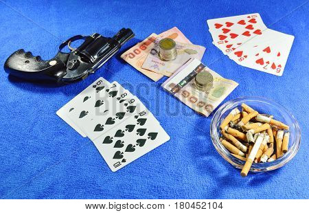 straight flush win poker game and gun with cigarette on blue velvet desk