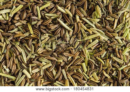 Dry leaves of rosemary and seeds of caraway. Food background. Closeup macro shot. Top view.
