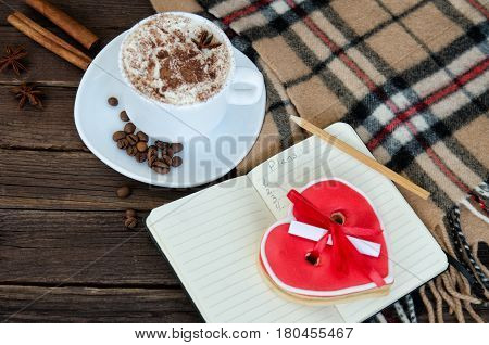 Cozy rest. Mug latte notepad with pencil gingerbread-heart plaid plaid and coffee beans. Top view