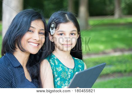 Closeup portrait family holding tablet using technology isolated outdoors outside background