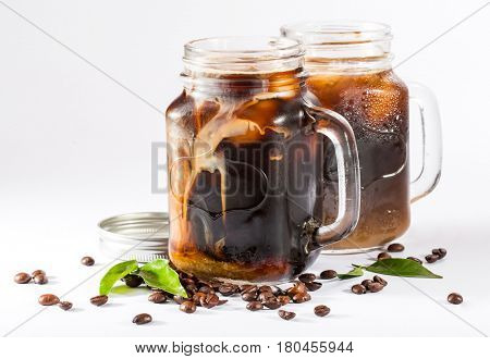 ice coffee in a tall glass with cream and coffee beans on a white background