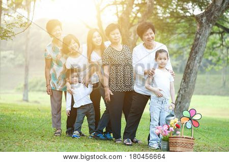Large group of Asian multi generations family playing at park, grandparent, parent and children, outdoor nature park in morning with sun flare.