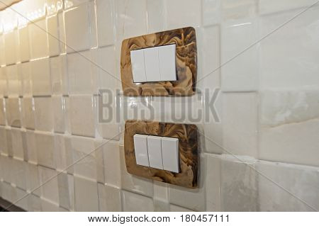 Closeup Detail Of Light Switches On A Kitchen Wall