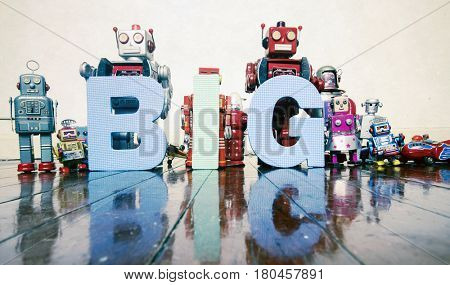 the word BIG held by old robot toys on wooden floor