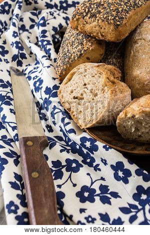 Whole Wheat Sandwich Buns, On Wooden Dish With Floral Kitchen Towel And Knife.