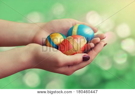 Female hands with Easter eggs on a bright green background.