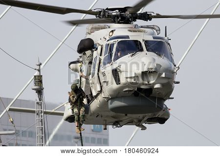 ROTTERDAM NETHERLANDS - SEP 3 2016: Anti-piracy demonstration with Dutch marines entering a vessel from a NH90 helicopter during the World Harbor Days in Rotterdam.