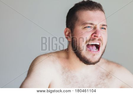 Portrait of a young emotional man screaming in anger