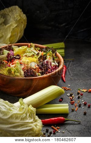 Wooden bowl with mix of salad freeze lollo rosso radicchio romano and iceberg with carrots on black background