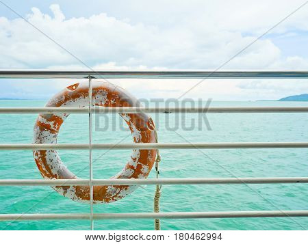 Life buoy hanging on railing in the ship