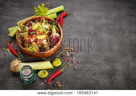Mix of salad freeze lollo rosso radicchio romano and iceberg with carrots on black background. With place for text