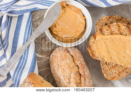 Peanut Butter In White Small Bowl And Knife, With Bread And Kitchen Towel.
