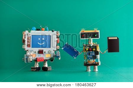 Computer repair renovation concept. Smiling monitor machine, robot serviceman with chip circuit storage memory card device. green background