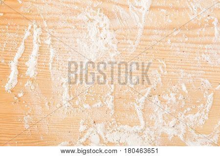 Messy floured wooden surface / background .
