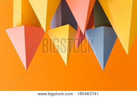Abstract colorful geometrical shapes background. Three-dimensional prism pyramid objects on orange paper. Yellow blue pink green colored solid figures, soft focus photo