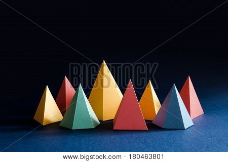 Colorful abstract geometric shape figures still life. Three-dimensional pyramid prism rectangular cube on black blue background. Yellow blue pink malachite colored objects textured paper surface.