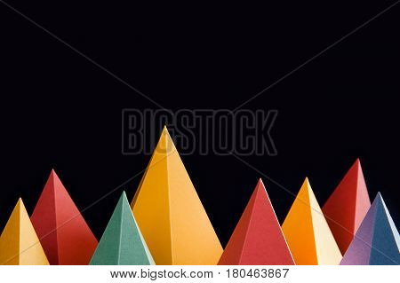 Colorful abstract geometric shapes on black background. Three-dimensional pyramid triangular. Yellow blue pink malachite colored objects. shallow depth field.