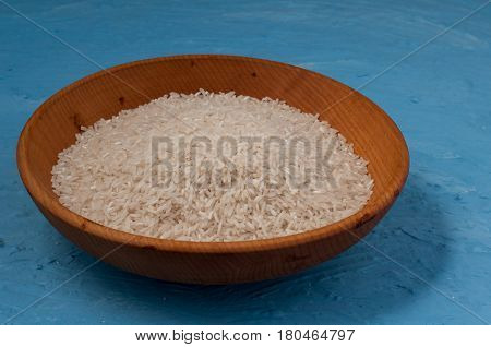 Plain Rice In Wooden Bowl Over Blue Background