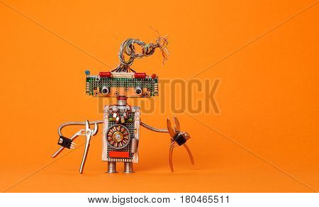 Funny robot electrician with pliers. Creative design robotic toy with electric wires hairstyle, electronic circuits, chip capacitors vintage resistors. Orange background copy text.