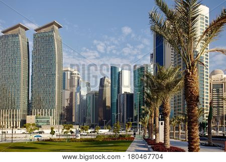 DOHA, QATAR - FEBRUARY 17, 2016: The high-rise district of Doha, seen from the road through the recently completed Hotel Park, and date palms in the foreground.