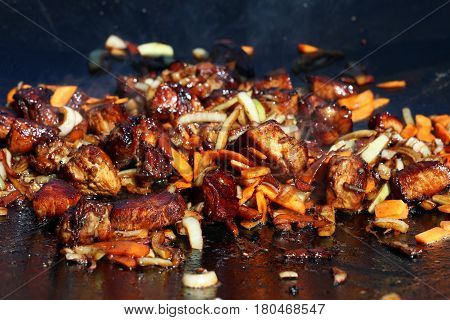 Hot cook meat onion carrot vegetable in smoke fry on cauldron pan. The ingredients for pilaf