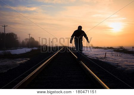 horizontal silhouette image of a man walking on the steel rail on the railroad track with a beautiful sunset in the background in early winter with room for text.