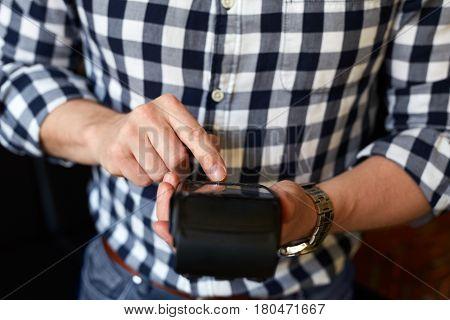 Man Entering Pin Number Using Payment Terminal