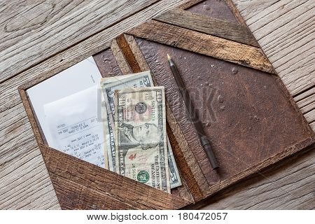horizontal image of a brown leather bill folder with a drink bill and American money in the slot on rustic table top.