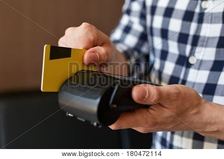 Close Up Of Male Hands Using Payment Terminal Paying With Credit Card
