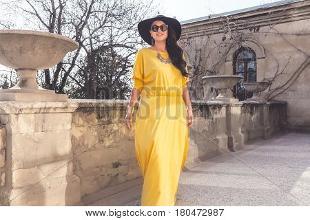 Young stylish woman wearing yellow maxi dress, black hat and sunglasses walking in the city street. Spring fashion outfit, elegant look. Plus size model.