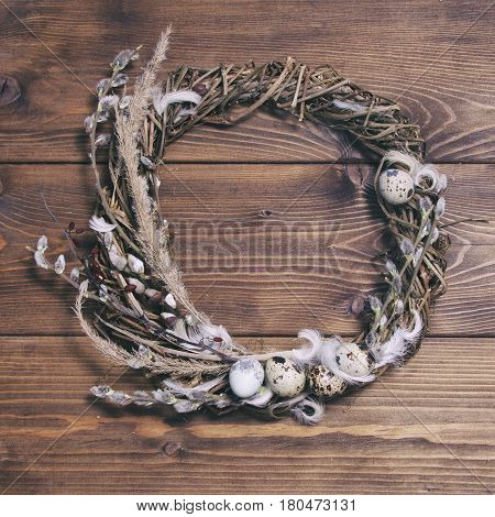 Easter wreath with willow twigs and quail eggs on a brown wooden background