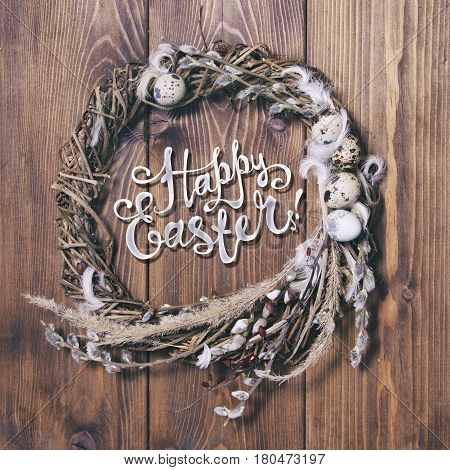 Happy Easter card. Wreath with willow twigs and quail eggs on wooden background
