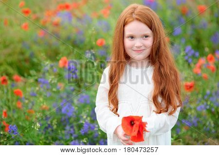 golden-haired girl standing among flowering meadows and smiles slyly