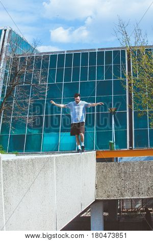 young man doing parkour walk on the edge of the concrete fence in urban space suuny spring summer day