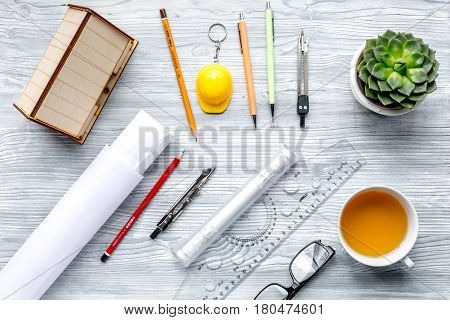 architect office with tools, cup and glasses in profession concept on light wooden desk background top view