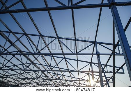 Galvanized steel roof truss construction frames with setting sun in the background