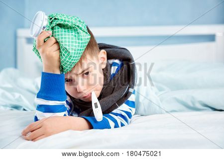 Ill boy lying in bed. sad child with fever and ice bag on head