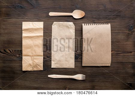delivery service set with paper bags and flatware on wooden desk background top view