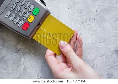 purchase with payment terminal by credit card on stone desk background top view
